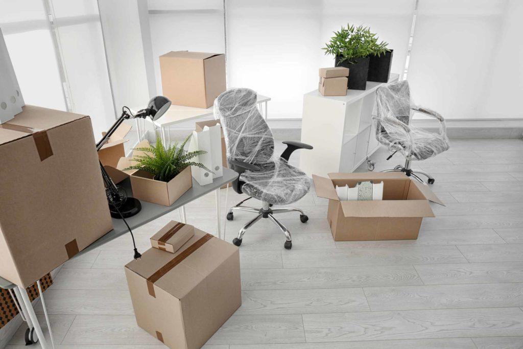 Für eine Haushaltsauflösung folierte Bürostühle und gepackte Umzugskisten